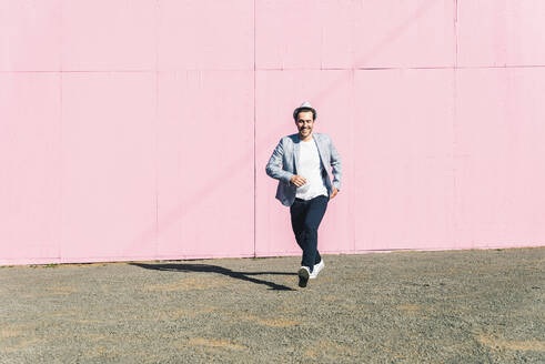 Young man in front of pink construction barrier, taking momentun - UUF17835