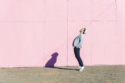Happy young man in front of pink construction barrier, standing on tiptoes, smiling - UUF17838