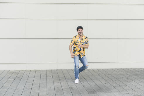 Young man wearing flat hat and aloha shirt, having fun - UUF17868