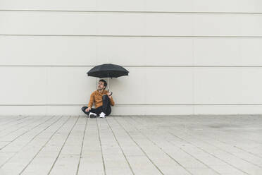 Young man with umbrella, sitting on ground, looking uncertain - UUF17883