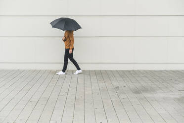 Young man with umbrella walking in the street - UUF17886