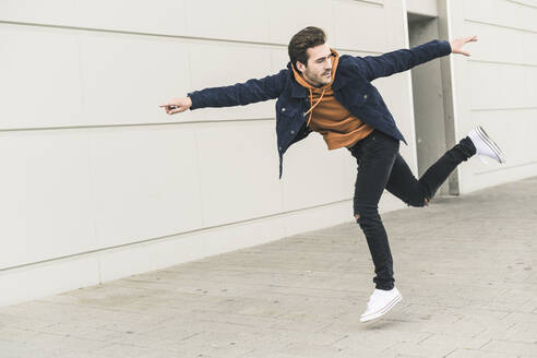Young man jumping in the street, pretending to fly - UUF17889