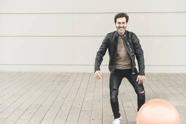 Young man in leather jacket, playing with a gym ball - UUF17892