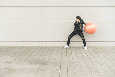Young man in leather jacket, playing with a gym ball - UUF17898
