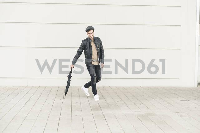 Young man walking around closed umbrella - UUF17901 - Uwe Umstätter/Westend61