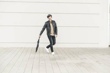 Young man walking around closed umbrella - UUF17901