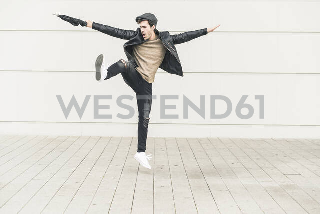 Young man dancing and jumping with closed umbrella - UUF17904 - Uwe Umstätter/Westend61