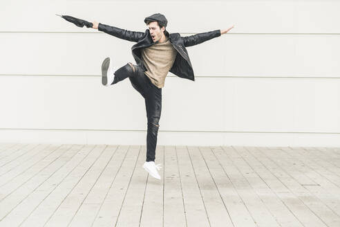 Young man dancing and jumping with closed umbrella - UUF17904