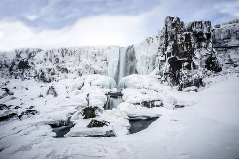 Waterfall pouring over icy cliffs in remote landscape - MINF12563