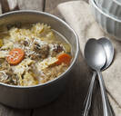 Close up of bowl of soup with spoons - MINF12623