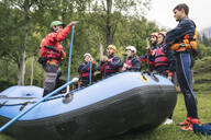 Instructor talking to group of friends at a rafting class - FBAF00720