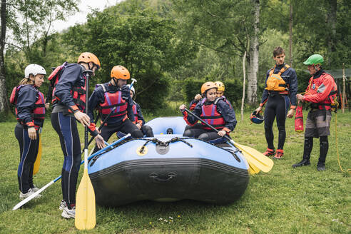 Group of friends preparing for a rafting trip - FBAF00726