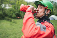 Portrait of a man in protective wear making a funny face drinking from bottle - FBAF00729