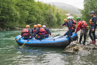 Group of people starting a rafting trip in rubber dinghy on a river - FBAF00732