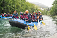 Group of people rafting in rubber dinghy on a river - FBAF00735