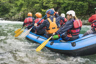 Group of people rafting in rubber dinghy on a river - FBAF00738