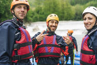 Happy friends at a rafting class posing at river shore - FBAF00741