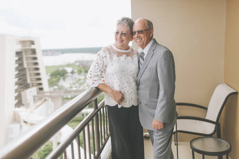 Smiling dressed up senior couple standing on balcony - CMSF00065