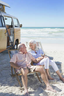 Happy senior couple sitting in lounge chairs on sunny beach near van - JUIF01402