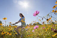 Smiling girl riding bicycle on path through sunny wildflower meadow - JUIF01420