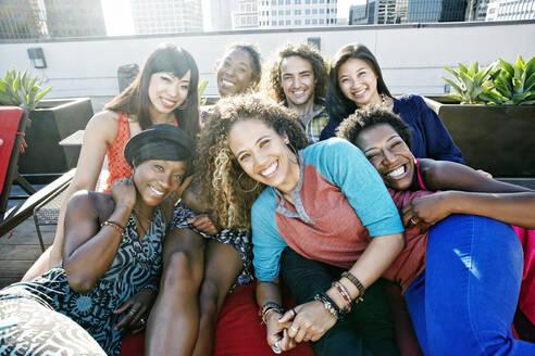 Friends hugging on urban rooftop - BLEF07074