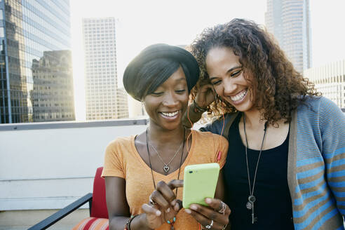 Women using cell phone together on urban rooftop - BLEF07077