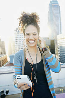 Mixed race woman listening to earbuds on urban rooftop - BLEF07080