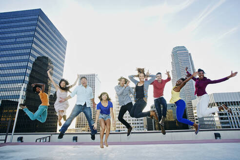 Friends jumping for joy on urban rooftop - BLEF07083