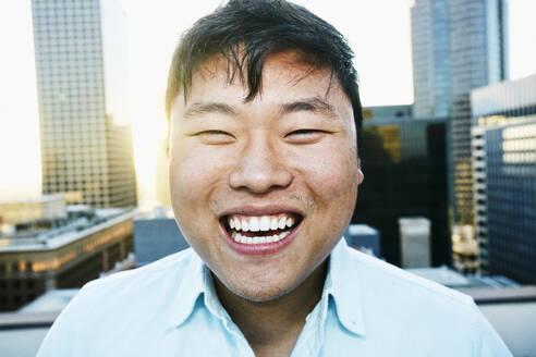 Korean man smiling on urban rooftop - BLEF07086