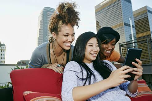 Women using digital tablet on urban rooftop - BLEF07089