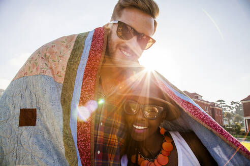 Couple wrapped in blanket smiling outdoors - BLEF07101