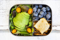 Lunchbox with salad, avocado and yellow tomato, cracker, and blueberry, from above - LVF08101