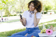 Relaxed woman with cell phone and earphones having a picnic in park - FMOF00696