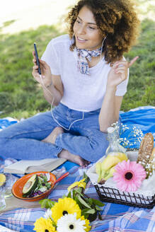 Relaxed woman with cell phone and earphones having a picnic in park - FMOF00699
