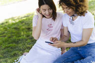 Two women using cell phone in park - FMOF00708