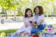 Two laughing women with cell phone and earphones in park - FMOF00711