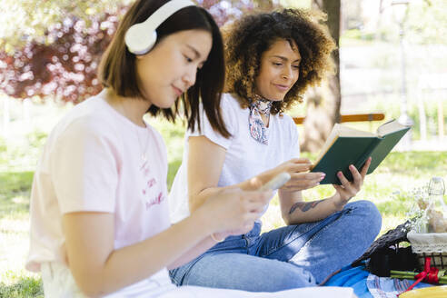Two women with book and headphones relaxing in park - FMOF00717