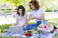 Two women having a picnic and using laptop in park - FMOF00720