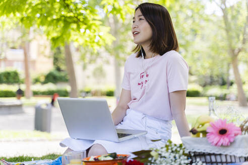 Young woman with laptop and earphones having a picnic in park - FMOF00723
