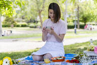 Relaxed woman with cell phone and earphones having a picnic in park - FMOF00726