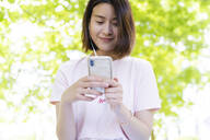 Relaxed woman with cell phone and earphones having a picnic in park - FMOF00729