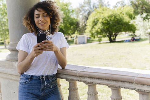 Smiling woman with cell phone and earphones in park - FMOF00735