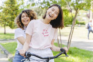 Two happy women on bicycle in park - FMOF00738