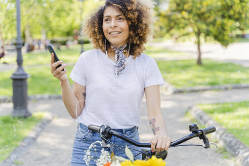 Smiling woman with cell phone, earphones and bicycle in park - FMOF00744