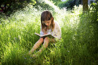 Little girl sitting on a meadow reading a book - LVF08107