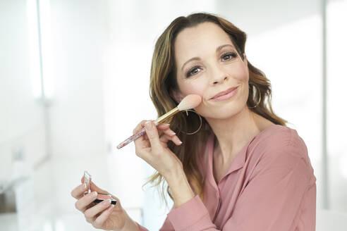 Frau beim schminken vor Spiegel mit Make-up Produkten, Studio, München, Deutschland - PNEF01600