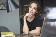 Woman with laptop at table at home thinking - PNEF01624