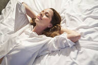 Smiling woman lying in bed with closed eyes - PNEF01654