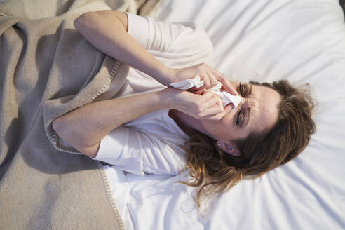 Woman lying in bed blowing her nose - PNEF01660