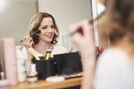 Portrait of smiling woman applying make up at the mirror - PNEF01663